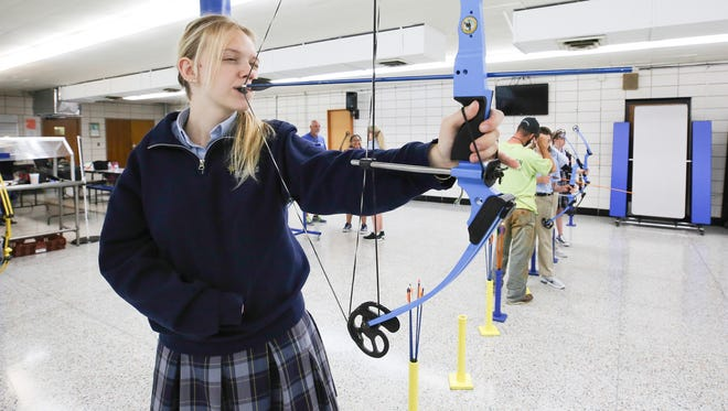 Bethlehem High School junior Faith Oakley, 16, takes aim on a target during practice in the school's cafeteria in Bardstown.  Oakley decided to take up archery in the fifth grade and has been collecting trophies in NASP (National Archery in Schools Program) and S3DA (State 3D Archery).  She placed 9th in the world NASP tournament this year.  Faith was born with a birth defect making her unable to use her right arm.  Instead, she uses a small, nylon strap to pull the bow back.