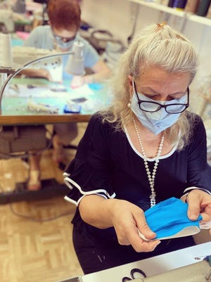 Anna Maria Arcudi, head seamstress at Jupiter Tailors, works on a face mask as part of the shop's donation effort for nurses and other healthcare workers in Florida and the New York City area.