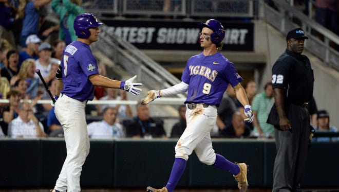 LSU Tigers center fielder Zach Watson (9) celebrates with infielder Jake Slaughter (5) after scoring during the seventh inning against the Florida Gators in game two of the championship series of the 2017 College World Series at TD Ameritrade Park Omaha.