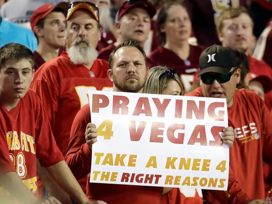 A fan holds a Praying for Vegas sign before an NFL football game between the Kansas City Chiefs and the Washington Redskins in Kansas City, Mo., Monday, Oct. 2, 2017. (AP Photo/Charlie Riedel)