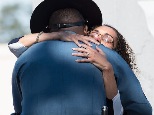 Louise Ballard, the wife of Delaware State Police Cpl. Stephen J. Ballard, hugs a Delaware State Police Trooper after placing a rose on the Delaware State Police Memorial during the Delaware State Police annual wreath-laying memorial ceremony at the Trooper's Memorial in Dover.
