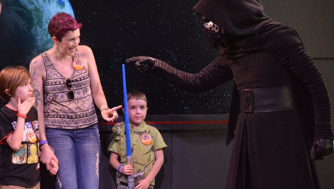 Kylo Ren touches the light saber of Rowan Peart while his mom, Maureen, and brother Kaerigan look on. The Peart family was able to go to Disney World thanks to the I Will Right Now Foundation in Brighton.