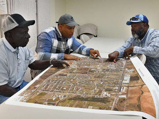 New Jerusalem Baptist Church deacons Billy Land, left, Johnnie Williams and Alonzo Nelson, right, plan out the locations of dumpsters and resources for Operation Fresh Start.