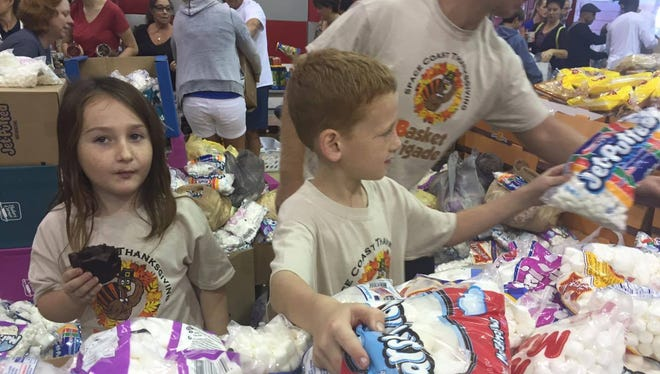 Riley Janik, of Viera, is on marshmallow duty as part of the 7th Annual Space Coast Basket Brigade. He is aided by his sister Myla, 6, and his father Michael Janik in the background.