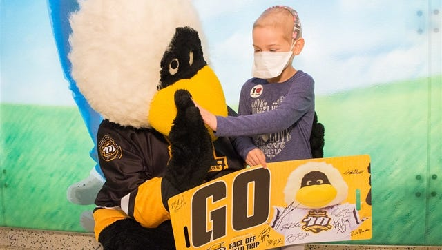 Team mascot RiverThing and a St. Jude patient share a high five during the RiverKings visit to St. Jude.