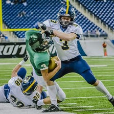 DeWitt safety Ben Zamiara smacks Zeeland West quarterback Casey Brinks out of bounds in the Division 3 state title game last season at Ford Field.