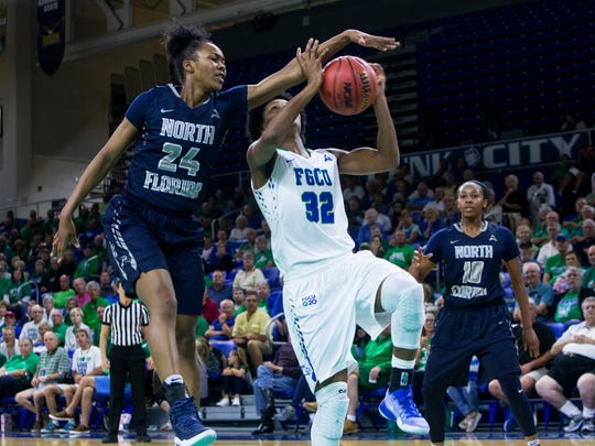 Florida Gulf Coast University junior, Rosemarie Julien, #32, attempts to drive the ball to the basket against a block from University of North Florida senior, Maiya Rumph, #24, during the ASUN quarterfinal game against the University of North Florida on Friday, March 3, 2017 at Alico Arena in Estero.