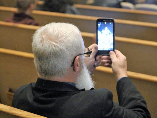 A member of the audience records a speech of a loved