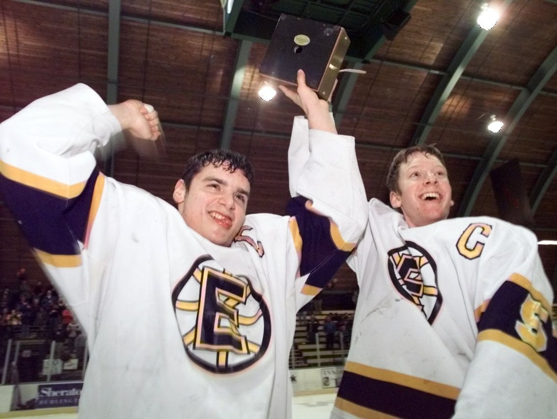 Essex captains Joe Galdi, left, and Jeff Carpenter raise the Division I high school boys hockey championship trophy after defeating Middlebury in 2001.