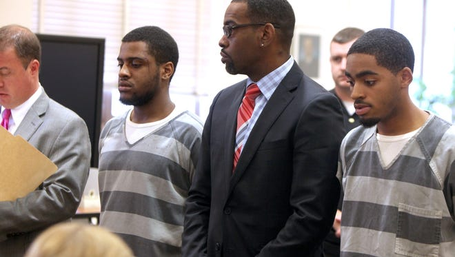 Robert Carpenter (left) and John Sanders stand with their defense attorney after they were indicted on aggravated murder charges in connection with the shooting death of 19-year-old Parris Hummons on April 16 in Bond Hill.