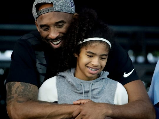 FILE - In this July 26, 2018, file photo former Los Angeles Laker Kobe Bryant and his daughter Gianna watch during the U.S. national championships swimming meet in Irvine, Calif. Federal investigators say wreckage from the helicopter that crashed last month and killed Bryant, his daughter and seven others did not show any outward evidence of engine failure, the National Transportation Safety Board said Friday, Feb. 7, 2020. (AP Photo/Chris Carlson,File)