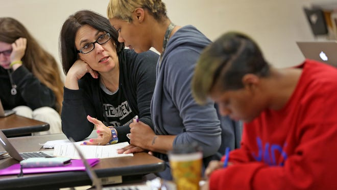 Math teacher Robin Clark, left, works with Carol Smiley, center, who is working next to her daughter Briana Tipton, right, in Algebra 1 class at Emmerich Manual High School. Clark started a program where she teaches parents in the same class as their children, ultimately to help them get their GED certificates. Smiley takes advantage of the program. The win-win situation brings families closer, adds more adult supervision in the class and promotes continued education in Clark's students' homes.