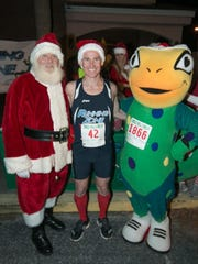 Jonathan Howse, a member ofthe Running Zone Race Team, has his photo taken with Santa Claus after the 2015 Jingle Bell 2-Miler.
