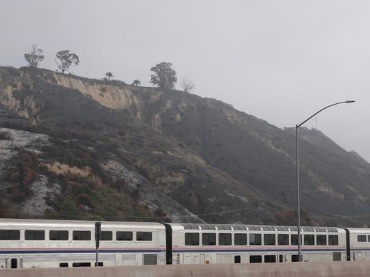 An Amtrak train passes charred hills near La Conchita recently.