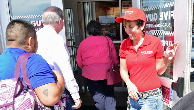 Judy Lekki, right, welcomes the first customers in line for lunch at the new Five Guys burgers and fries restaurant Tuesday, at 924 Norland Av., Chambersburg.