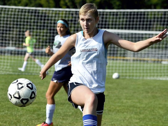 Maddie Hill runs soccer practice drills during her