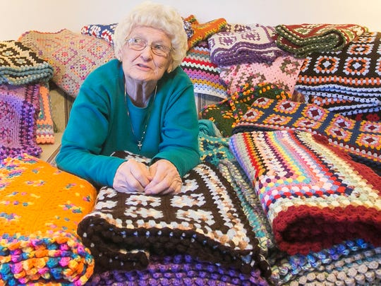 Surrounded by 30 afghans she crocheted, Janet Clark  poses at her Dover Township home Wednesday, Nov. 23, 2016. Clark, who has been crocheting since the 1960s, will soon donate the afghans  to the Walter Reed National Military Medical Center in Bethesda, Maryland. Amanda J. Cain photo