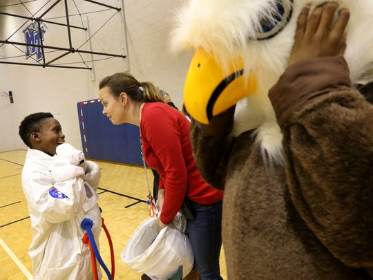 E.J. Turner, left, a fourth-grader at Hobgood Elementary gets some words of encouragement from his teacher, Ashlee Barnes, center, before playing a mascot game of basketball during half-time of the Education Day game Thursday. JaTavious Hathaway, right, a fifth-grader at Mitchell-Nelson Schools puts on his eagle mascot head as he gets ready for the half-time game.
