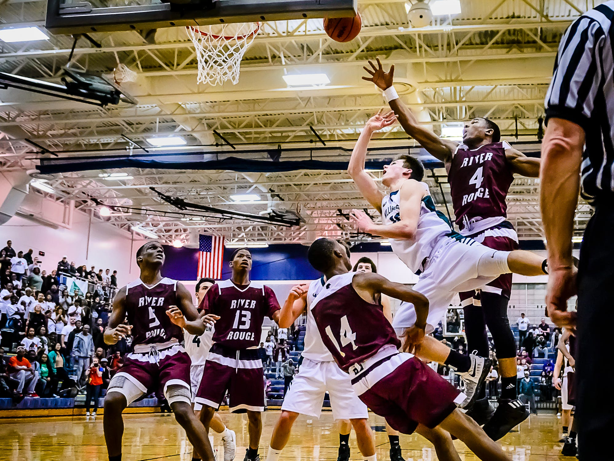 Mitchell Cook ,second from right, of Williamston lays the ball up and in as he collides with Jayvien Torrence ,14, of River Rouge with 18 seconds remaining in their Class B state quarterfinal game and the score tied at 51 Tuesday March 21, 2017 at Chelsea High School in Chelsea. The basket was waived off as Cook was charged with a player control foul.