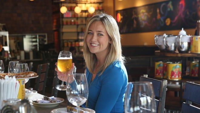 Journal News food writer Megan McCaffrey lifts a beer at Fortina in Rye Brook.