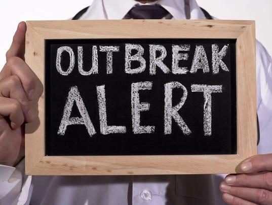 Outbreak alert text written on blackboard in doctor hands, epidemic warning