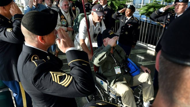 Billy Huff Jr., US Army, returns a salute from his chair as he is wheeled to the HonorAir Knoxville flight leaving McGhee Tyson Airport on the 21st flight to Washington, D.C.,  on Wednesday, June 8, 2016. One hundred fifty East Tennessee Vietnam War veterans traveled to see the memorials built to honor their sacrifices in a program established and presented by Eddie Mannis of Prestige Cleaners/Prestige Tuxedo.