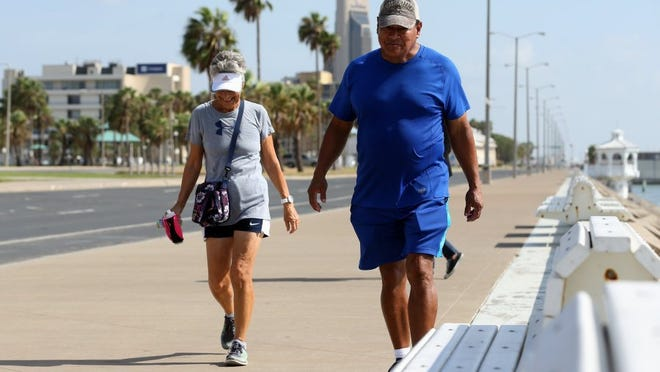 GABE HERNANDEZ/CALLER-TIMES Cheryl Jacobson (left) and Mario Hernandez walk along the sea wall Friday, Aug. 12, 2016, in Corpus Christi.