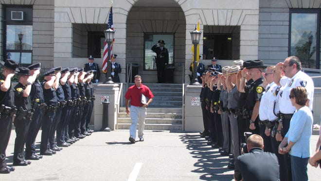 Elmira Deputy Police Chief Joseph Kain is saluted by his colleagues, sheriff's deputies, state police and others in area law enforcement as he leaves Elmira City Hall Friday afternoon following his retirement that day.