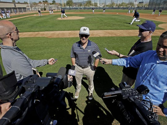 Milwaukee Brewers owner Mark Attanasio talks to reporters during a spring training workout  in Phoenix.