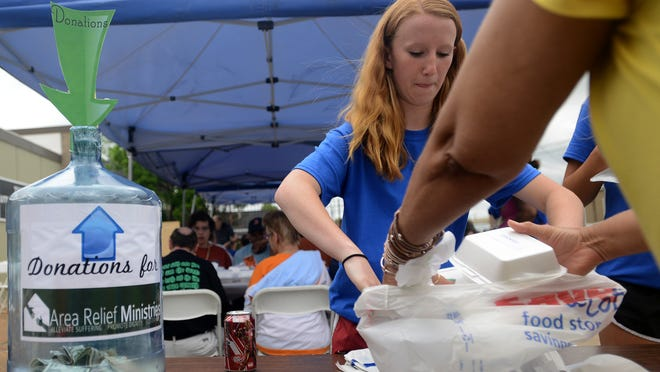 Madison Cooper helps a member of the community with her food Friday during Teel & Maroney's annual community cookout. The event was held to benefit Area Relief Ministries.