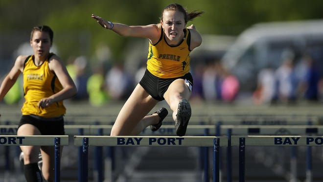 Green Bay Preble senior Hayley Winzenried soars over a hurdle while competing in the 100-meter hurdles during a WIAA Division 1 sectional track and field meet at Bay Port High School in Suamico on May 26.
