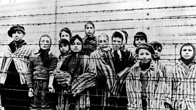 Children wearing concentration camp uniforms stand behind barbed wire fencing at Auschwitz in January 1945.