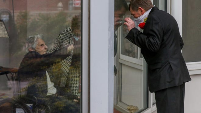 David 'Mick' McGovern greets his mother, Estelle McGovern, through a window at Linn Health & Rehabilitation in East Providence just before he married Susan Nestell on the nursing home's patio April 18 -- a time when visitation inside any nursing home in Rhode Island was prohibited.