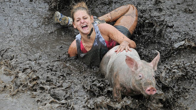 Jessy Liebelt of Sheboygan Falls slips in the mud while chasing a pig in the 2013 Hog Wild in Dundee.