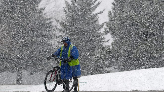 A woman walks her bike through the snow on Lemay Avenue in March.