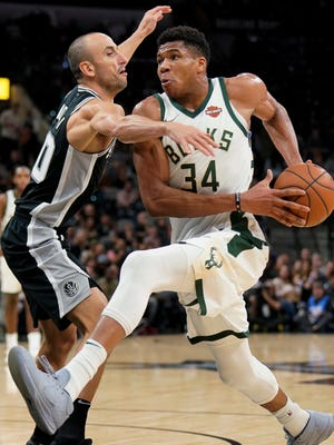 Giannis Antetokounmpo of the Bucks, who scored a game-high 28 points, drives to the basket against Spurs veteran guard Manu Ginobili during the first half of an on Friday night.