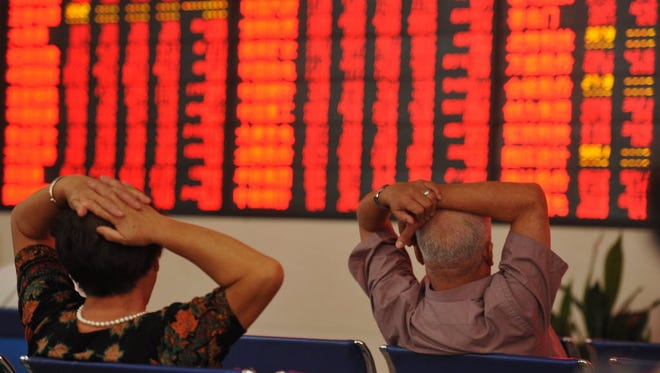 Investors observe stock market data at a stock exchange hall on Aug. 10 in Fuyang, Anhui Province, China.