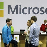 Microsoft Corp. retail store employees and guests mingle at a pop-up Microsoft Store during Microsoft's annual meeting of shareholders, in Bellevue, Wash.