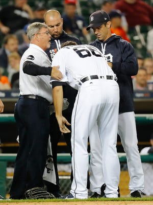 Tigers pitcher Jeff Ferrell (66) heads to the dugout with trainers and manager Brad Ausmus, right, after being hit by a Athletics DH Ryon Healy line drive in the eighth inning of the Tigers' 8-3 loss to the A's on Monday, Sept. 18, 2017, at Comerica Park.