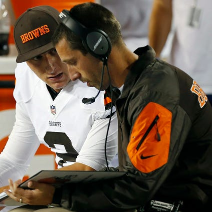 Aug 18, 2014; Landover, MD, USA; Cleveland Browns quarterback Johnny Manziel (2) talks with Browns offensive coordinator Kyle Shanahan (right) on the bench against the Washington Redskins in the second quarter at FedEx Field. The Redskins won 24-23. Mandatory Credit: Geoff Burke-USA TODAY Sports