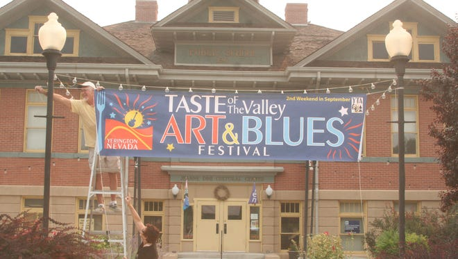 """Roy Enochson, top left, Yerington Theatre for the Arts facilities and galleries, and Debbie Arrighi, YTA executive director, hang a banner in front of the Jeanne Dini Center publicizing the local arts' organization's annual """"Taste of the Valley"""" Art & Blues Festival on Sept. 13 and 14, 2013, which features several bands, food and other entertainment."""