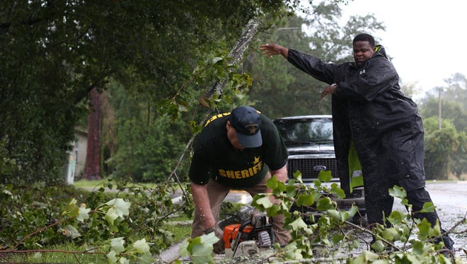 LCSO deputies Pat Kennedy (left) and Richard Ash clear a tree from Bradford Road Monday morning. They started clearing roads at 5 am the morning after Irma blew through Tallahassee.