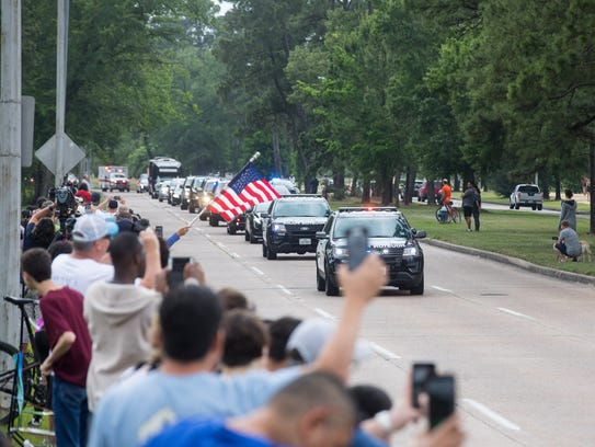 People line the streets in Memorial Park as the funeral