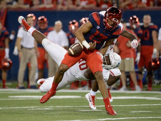 Arizona Wildcats quarterback Brandon Dawkins (13) loses the ball as he tackled by Houston Cougars defensive tackle Ed Oliver (10) during the second half at Arizona Stadium.