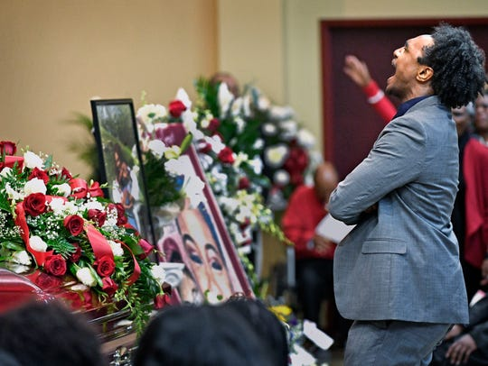 DiAngelo Groves shouts and dances in front of the casket