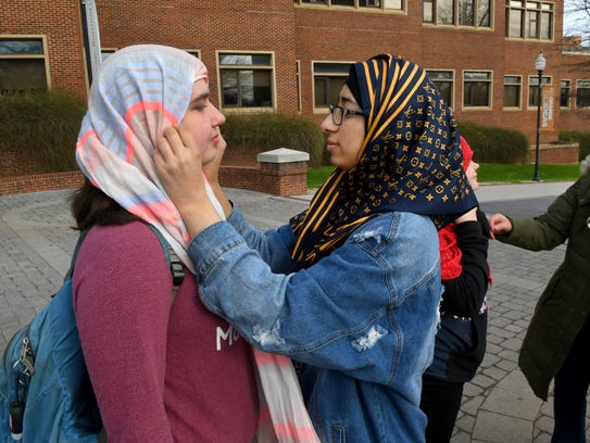 UT student Kate Conway tries on a hijab with help from