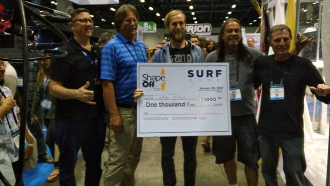 Jordan Brazie, center, was the winner of the 2017 Surf Expo Shape-off competition. He receives a check for $1,000 for his victory.