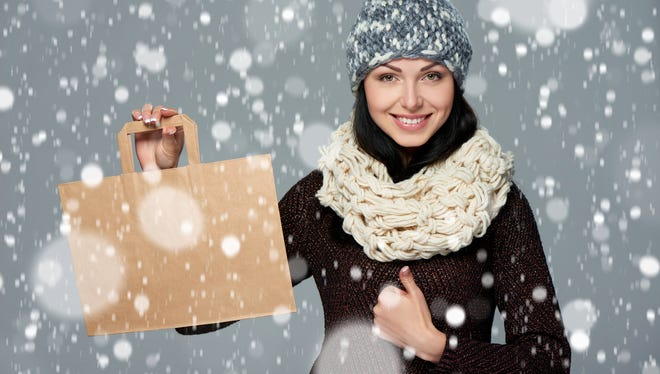 Winter holidays sale, shopping, Christmas concept. Portrait of smiling woman wearing warm winter hat and muffler showing shopping bag with empty copy space and gesturing thumb up over snow background