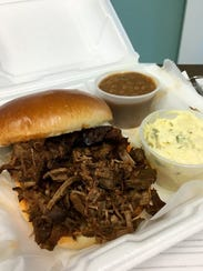 A take-out order of the beef brisket sandwich with potato salad and baked beans on the side at I Burnt Mine, 3802 U.S. 41 E.