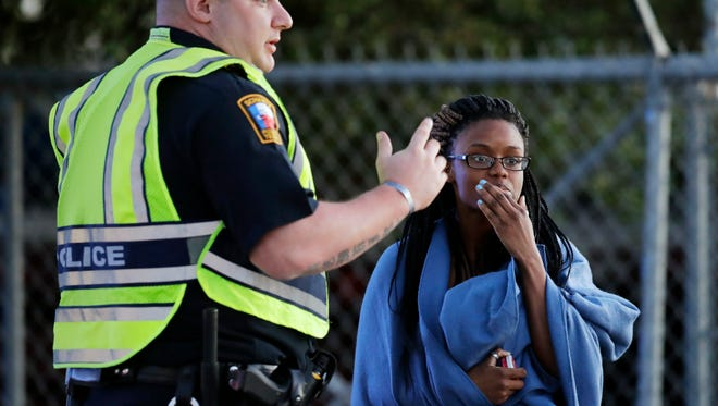 An employee wrapped in a blanket talks to a police officer after she was evacuated at a FedEx distribution center where a package exploded, Tuesday, March 20, 2018, in Schertz, TX.  Authorities believe the package bomb is linked to the recent string of Austin bombings.